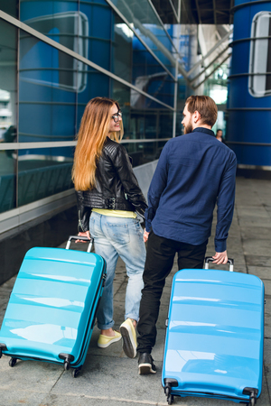 Cute couple is walking with suitcases outside in airport. She has long hair, glasses,  yellow sweater, jacket. He wears black shirt, beard. They are holding hands and smiling. View from back. Stock Photo