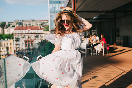 Activ girl  in sunglasses is listening to music through headphones on the terrace. She wears a white dress with bare shoulders, red lipstick and hat . She is dancing like crazy