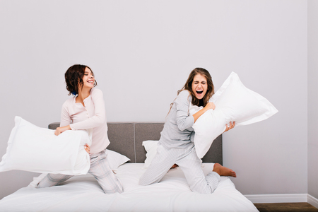 Two pretty girls having pajamas party. They fighting with pillow fight on bed