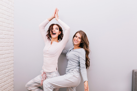 Two young pretty girls in night pajamas having fun  in on grey wall background. Girl with curly hair trying doing yoga