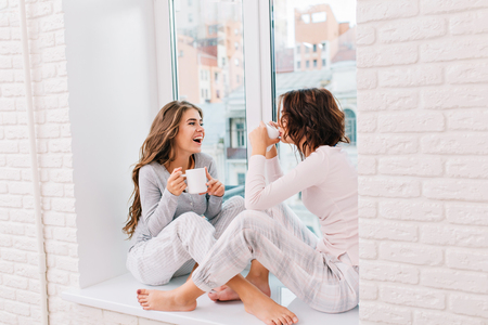 Two pretty girls in pajamas sitting on window in light room. They drinking tee and smiling to city outside