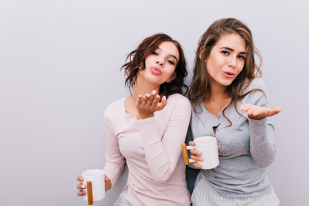 Portrait two beautiful  girls in pajamas with white cups on grey wall background. They send kisses to camera