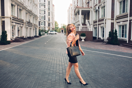 Fashionable blonde girl with long hair walking in black dress around British quarter. She holds coffee, smiling to camera Stock Photo