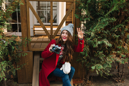 Pretty girl with long hair in red coat and knitted hat sitting on wooden stairs. She holds camera and looks to side