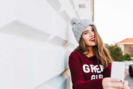 Portrait pretty girl with long hair in marsala sweater making selfie on grey wall background. She wears knitted hat and has red lips Stockfoto
