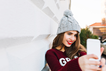 Portrait young girl with long hair in marsala sweater making selfie on grey wall background on street.  She wears knitted hat and has red lips