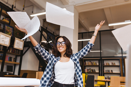 Joyful young brunette woman in black glasses throwing papers above in library. Cheerful mood, smiling to camera, good results, expressing positive true emotions Reklamní fotografie