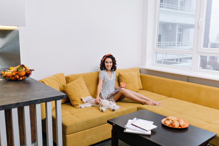Relax time in modern apartment of enjoyed, happy young woman chilling on orange couch. Magazine, cup of tea, home pets, joyful mood, smiling, true emotions