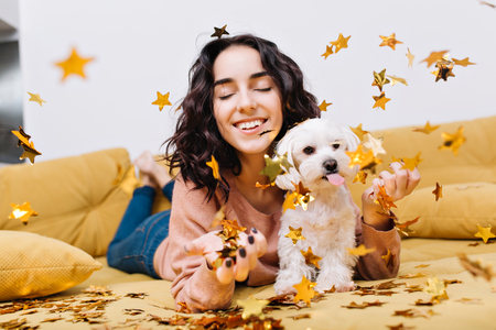 Portrait joyful amazing young woman smiling with closed eyes in falling golden tinsels. Chilling on couch with home pets, little white dog, smiling, cheerful mood, relaxation