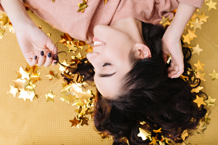 Closeup portrait from above young joyful woman with cut curly hair having fun in golden tinsels on couch at home. Lovely cosiness of pretty model, expressing positivity 스톡 콘텐츠