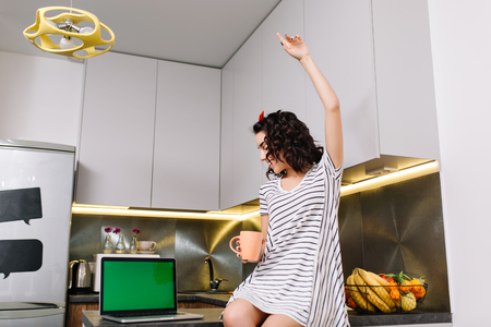 Happy morning in kitchen in modern apartment of joyful young woman in dress having fun on table. Laptop with green screen, tea, brightful emotions, smiling, true emotions
