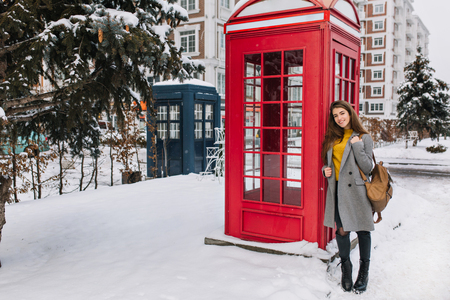 Outdoor portrait of fashionable brunette girl with backpack posing beside red call-box during weekend in England. Full-length photo of refined woman in gray coat smiling near phone booth in winter.. Imagens