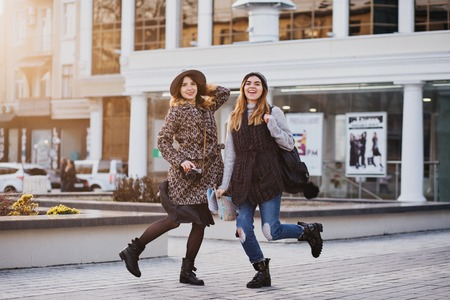 Two fashionable joyful smiling girls jumping over city background. Stylish look, travelling together, wearing modern trend clothes, walking with coffe to go, expressing positive emotions
