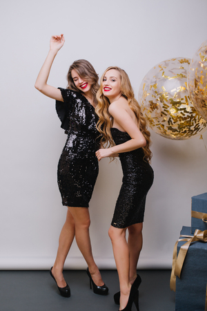 Happy brightful party celebration of two amazing attractive young women in luxury black dresses having fun on white background. Big balloons full golden tinsels, presents, expressing positivity Stock fotó