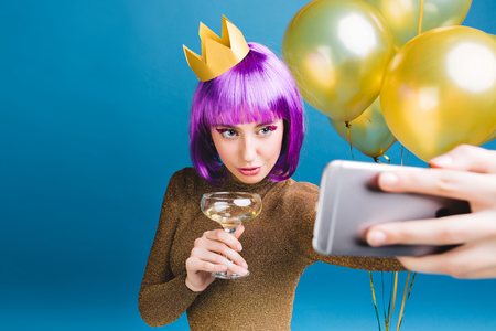 Charming young woman with purple haircut, crown on head making selfie portrait on blue background. Golden balloons, champagne, celebrating new year party, luxury dress, tinsels makeup