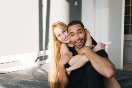 Portrait joyful couple in love of cute young woman with long blonde hair hugging handsome guy on bed. Sunny morning at home, modern apartment, having fun, romance