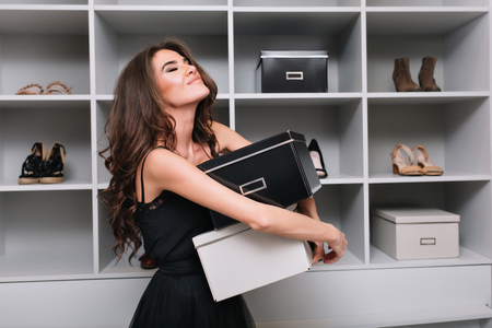 Pretty young woman hugging boxes of shoes around stylish dressing room, wardrobe. Shes very happy, pleased, has closed eyes, she bought what she wanted. She wearing black dress, has long curly hair. Stockfoto - 123080333