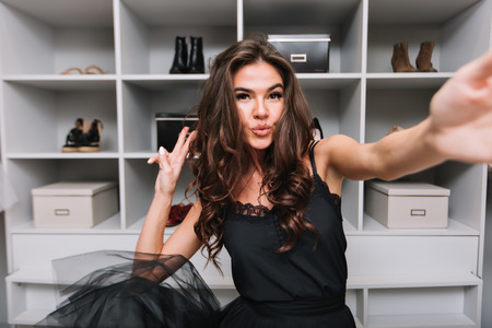 Happy gorgeous young woman with curly brown hair, dancing and taking selfie in her dressing room. She showing kiss to camera. She enjoying good day. Wearing black dress. Reklamní fotografie