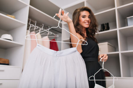 Pretty young woman with brown curly hair holding white beautiful skirt on hanger, happy to have nice clothes. Luxury wardrobe on background. Model with fashionable look, wearing black elegant dress. Stockfoto - 123080263