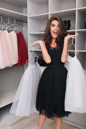 Gorgeous young woman with happy look holding beautiful white fluffy skirts in big nice wardrobe, pleasantly surprised, shocked, cheerful. Fashionable model wearing black dress, elegant look.