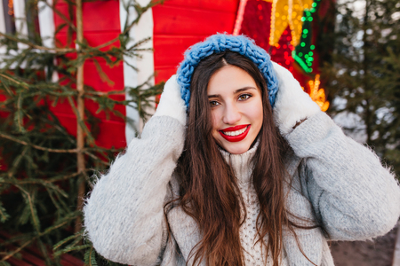 Close-up portrait of enthusiastic girl in blue hat posing with happy face expression in front of christmas trees. Outdoor photo of glamorous woman with  dark hair standing near new year decoration. Reklamní fotografie