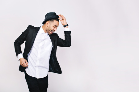 Attractive young man in suit dancing, having fun on white background. Stylish outlook, hat, successful businessman, happy, expressing true positive emotions, funny. Place for text Imagens
