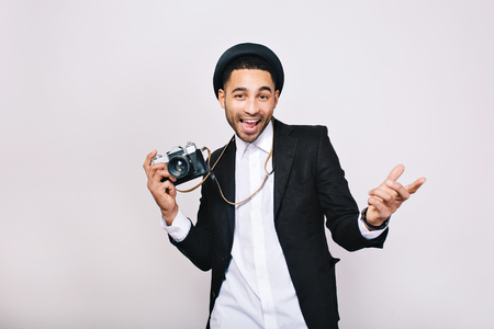 Happy handsome young man in suit, hat having fun with camera on white background. Fashionable look, modern photographer, tourist, weekends, leisure, travelling, expressing positive emotions