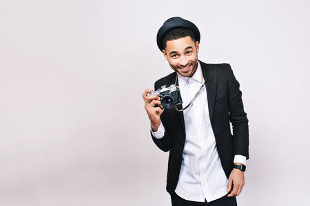 Smiled joyful young man in suit, hat on white background. Fashionable look, modern, tourist with camera, travelling, having fun, expressing positive emotions. Place for text