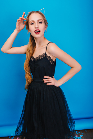 Pretty young woman with long blonde hair on party, masquerade, carnival posing to camera at blue background. Wearing beautiful black dress, diadem with cat ears in diamonds on head. Stock Photo