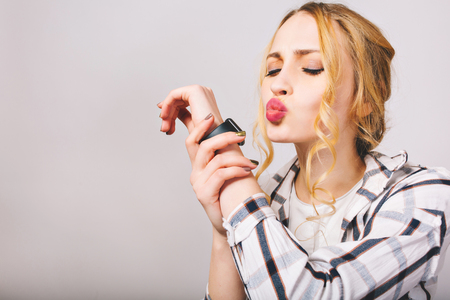 Close-up portrait of young attractive woman with everyday make-up holding her hand with black wristwatch. Curly pretty girl in striped shirt posing with eyes shut isolated on the white background.