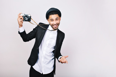 Happy handsome guy in suit, hat having fun with camera on white background. Excited, expressing true positive emotions, smiling, travelling, photographer, success. Place for text