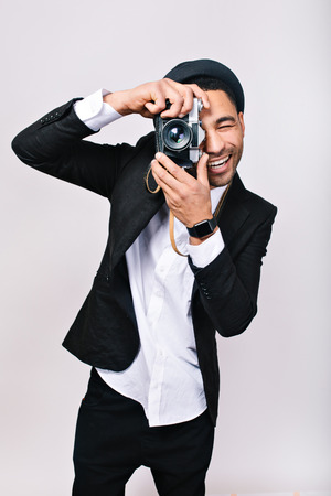 Joyful smiled guy in hat, suit making photo on camera, having fun on white background. Fashionable man, photographer, happy tourist, lovely hobby, leisure, free time, excited person, happiness