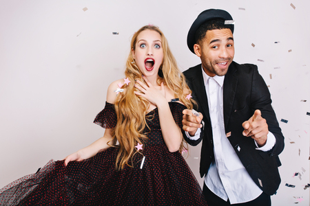 Portrait astonished excited woman with long blonde hair in luxury dress with funny handsome guy having fun in tinsels on white background. Celebrating great party, smiling, Valentine s day Stock Photo