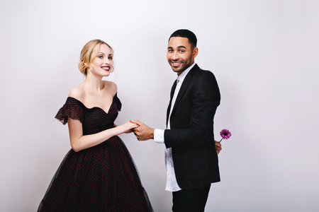 Charming couple in-love celebrating Valentines day on white background. Attractive woman in luxury evening dress, elegant handsome man in tuxedo with flower behind back. Love, smiling, sweathearts