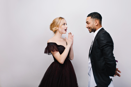 Lovely sweathearts of attractive astonished young woman in luxury evening dress and handsome man in tuxedo dating on white background. Valentines Day, surprise, true emotions, gift, love, together Imagens