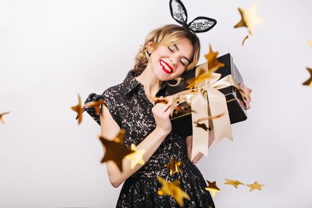 Crazy party time of beautiful women in elegant black dress with gift box celebrating birthday,sparkling gold confetti, having fun, dancing. Emotion face,red lips, eyes closed.