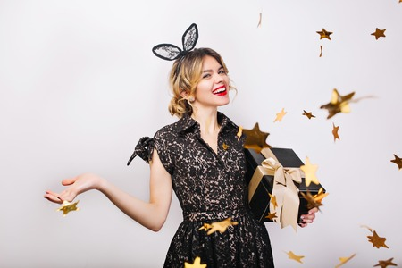 Happy time, young smiling woman on white background with gift box celebrating, wearing black dress and crown, happy carnival disco party, sparkling gold confetti, having fun, smiling. 版權商用圖片