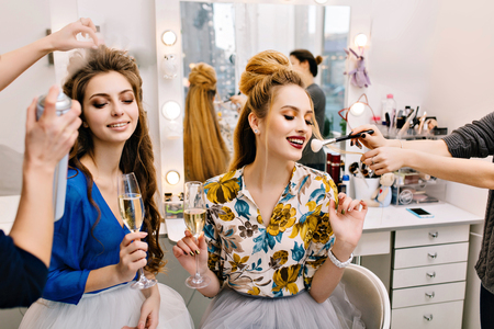 Two joyful young women with luxury look drinking champagne during preparation to party in hairdresser salon. Smiling, expressing positivity, making hairstyle, makeup, fashionable models, happiness Banco de Imagens