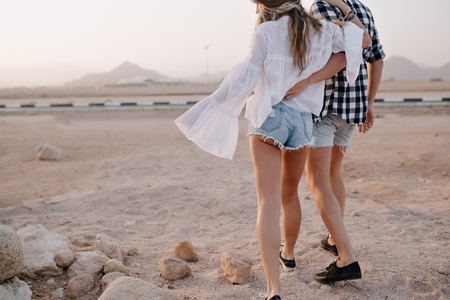 Long-haired girl with  guy in trendy denim shorts walks in an embrace near the highway early in the morning. Stylish couple hugging and enjoys beautiful desert views on a date in the summer evening.