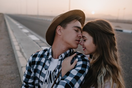 Long-haired attractive girl gently embracing her boyfriend in stylish shirt with eyes closed on blur background. Young man wearing hat going to kiss his girlfriend in nose walking across the road