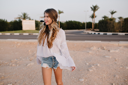 Slim long-haired girl in vintage white blouse walking on the sand with exotic palm trees on background. Charming young woman with cute hairstyle spending time outside and looking away with interest