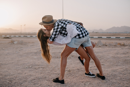 Stylish young man in hat and long-haired slim girl dancing on the sand and kissing at sunset. Portrait of cute embracing couple in denim shorts, spending time together on mountain background