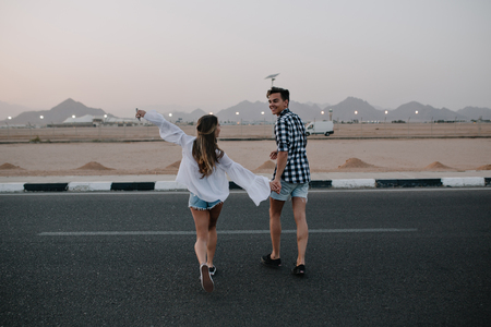 Guy in denim shorts and long-haired girl in trendy blouse running across the road and enjoys mountain view. Laughing young couple holding hands walking on highway and having fun outside in summer