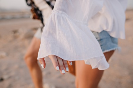 Graceful girl in vintage blouse and denim shorts with trendy white manicure having fun outside running on the sand. Couple spending time together dancing in desert. Body part, blur background, outfit Stock Photo