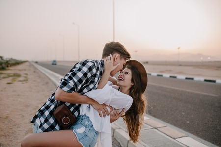 Laughing guy with retro camera dances with his long-haired girlfriend near the highway, waiting for a ride. Beautiful loving couple having fun outside and enjoys life at sunset, hugging at the road Stock Photo