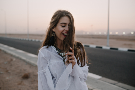 Attractive smiling long-haired girl posing with eyes closed while walking down the road in summer evening. Portrait of beautiful young happy woman in tunic enjoys vacation and spending time outside Stock Photo