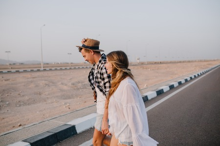 Graceful long-haired girl in white shirt and boy in hat walking down the highway holding hands and smiling. Stylish couple crosses the road and talking about travel under open sky in early morning Stock Photo