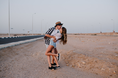Slim girl standing in denim shorts on one leg, gently kisses her boyfriend on beautiful desert background. Stylish young man embracing his girlfriend, posing near the highway in summer vacation Stock Photo