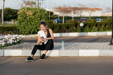 Amazing joyful pretty young woman in sportswear, with long curly hair chatting on phone on street in summer morning time. Workout, cheerful mood, happiness, sunrise, joy, healthy lifestyle, workout Stock Photo