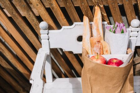 Photo of paper bag from grocery with bakery products, red apples and bouquet of purple flowers.  Fresh food from supermarket lying on the white bench in front of wooden fence.  Meal shopping